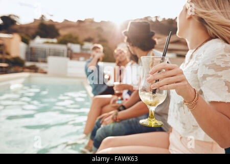 Woman holding a cocktail glass while sitting on the edge of swimming pool with friends. Young people enjoying a - Stock Photo