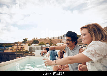 Young man pouring champagne in glass of his girlfriend while partying by the swimming pool. Young people having - Stock Photo