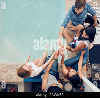 Top view of group of friends toasting at party by a swimming pool. High angle shot of young people sitting by the - Stock Photo