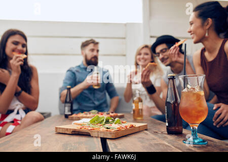 Group of multi-ethnic friends enjoying pizza and beer in party. Young people having a party. Focus on pizza and - Stock Photo