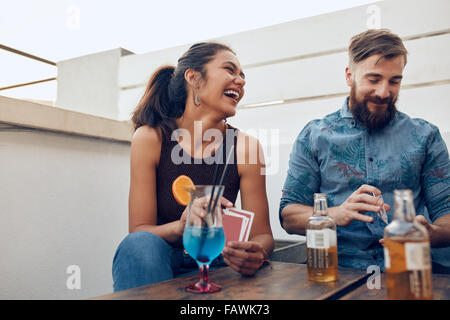 Couple sitting by a table partying and playing cards. Happy young man and woman playing cards during a party. - Stock Photo