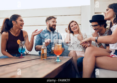 Portrait of happy young people sitting together and laughing. Multiracial friends enjoying at a party with cocktails - Stock Photo