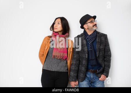 Persian man and Tibetan woman holding hands and leaning against a wall facing away from each other; Toronto, Ontario, - Stock Photo