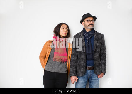 Persian man and Tibetan woman holding hands and leaning against a wall, man looking away while woman is looking - Stock Photo