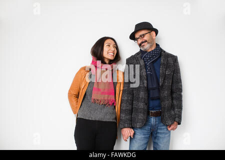 Persian man and tibetan woman leaning against a wall smiling and holding hands; Toronto, Ontario, Canada - Stock Photo