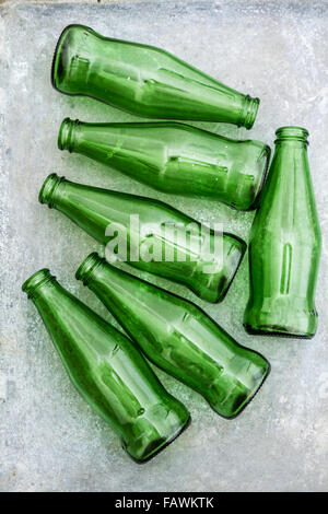 Group of green opened bottles on old gray tray - Stock Photo