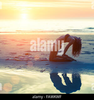 Young girl performs yoga exercises on the beach during sunset. Yoga, fitness and a Healthy lifestyle. - Stock Photo