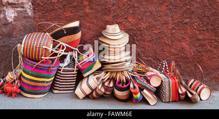 Woven souvenirs on display on a sidewalk against a wall; San Miguel de Allende, Guanajuato, Mexico - Stock Photo