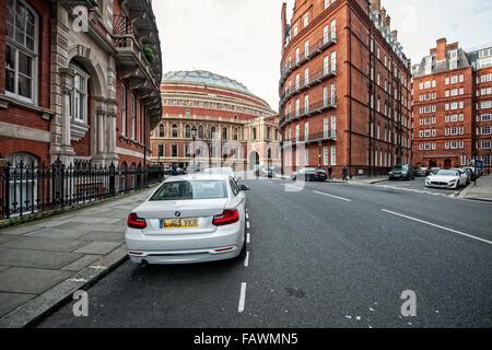 Brick row houses at Kensington Gore Street with Royal Albert Hall in the back, Kensington, London. - Stock Photo