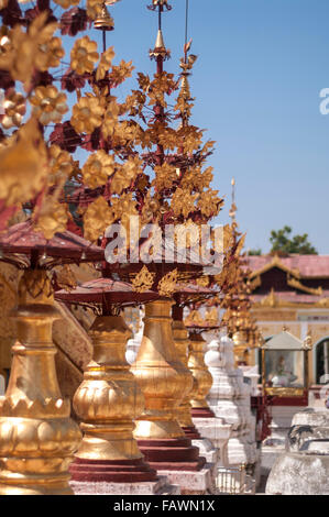 Shwezigon pagoda in Nyaung-U/Bagan, Myanmar. Richly ornamented decorations as a row of small spires. Shallow depth - Stock Photo