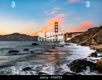 Golden Gate Bridge, Marshall's beach, sunset, rocky coast, San Francisco, USA - Stock Photo