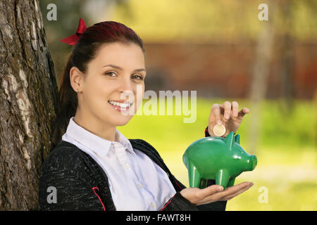 Saving during sunny days so when the rainy ones come. Beautiful young female student leaning on a tree in the park, - Stock Photo