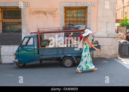 Men looking woman, view of two men looking at a young woman in a long summer dress as she walks past a fruit vendors' - Stock Photo