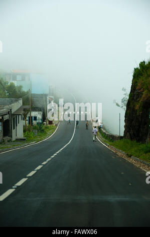 Asphalt road going down to fog and mist - Stock Photo