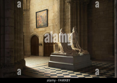 The statue of a royal couple caught in beautiful light in the grandiose Basilica of Saint Denis; Paris, France - Stock Photo