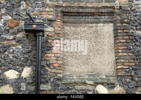 Brick wall with a window that has been blocked up with bricks, with a black pipe running down the wall - Stock Photo