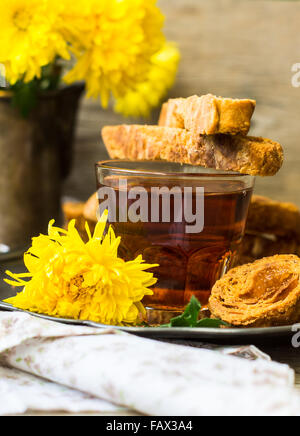 Biscotti on vintage plate with glass of tea and yellow flowers on old wooden rustic table - Stock Photo