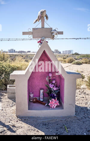 small roadside shrine with toy animals & artificial flowers & beachfront condos in distance honors child killed - Stock Photo