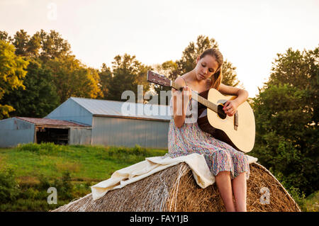 Girl with guitar on farm - Stock Photo