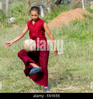 A young monk plays with a soccer ball; Punakha, Bhutan - Stock Photo