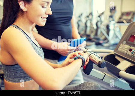 close up of woman setting heart-rate watch at gym - Stock Photo