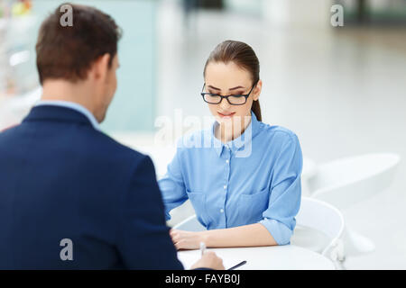 Two employees at the table working together. - Stock Photo