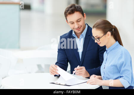 Nice-looking colleagues doing office paperwork - Stock Photo
