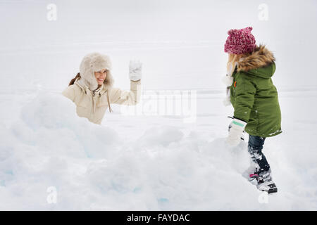 Winter outdoors can be fairytale-maker for children or even adults. Portrait of happy mother and child playing snowball - Stock Photo