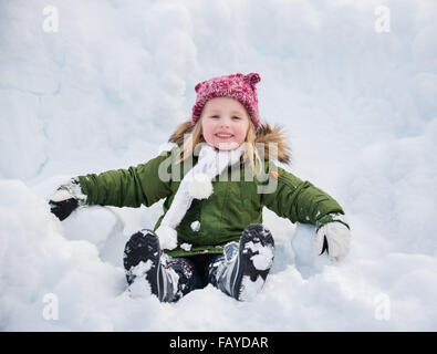 Winter outdoors can be fairytale-maker for children or even adults. Happy child in green coat sitting on the snow. - Stock Photo
