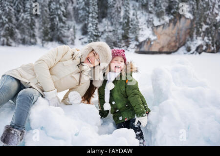 Winter outdoors can be fairytale-maker for children or even adults. Portrait of smiling mother and child playing - Stock Photo