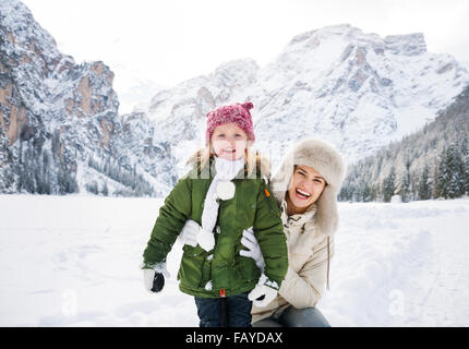 Winter outdoors can be fairytale-maker for children or even adults. Portrait of smiling mother and child outdoors - Stock Photo