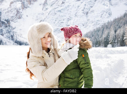 Winter outdoors can be fairytale-maker for children or even adults. Smiling mother pointing on something to child - Stock Photo