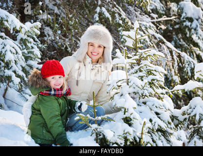 Winter outdoors can be fairytale-maker for children or even adults. Happy mother and child outdoors among snowy - Stock Photo