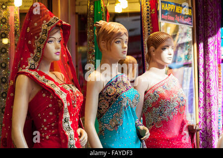 Three mannequins dressed in colourful, embroidered Saris outside a shop in India - Stock Photo