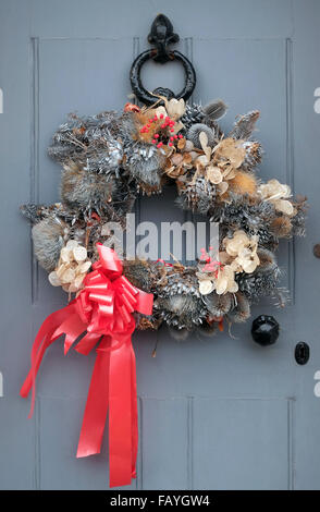 decorative christmas wreath hanging on grey door - Stock Photo