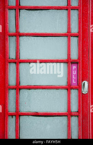 Old red telephone box covered in frost. UK