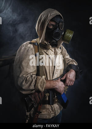 Armed man in protective mask. Stalker. Post-apocalyptic fiction - Stock Photo