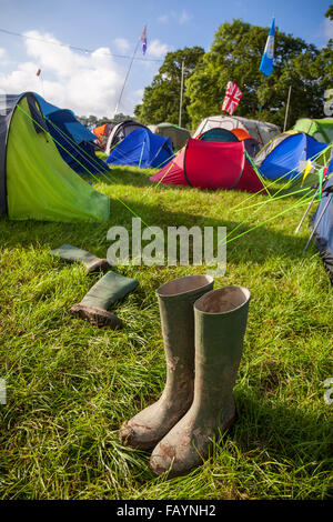 A pair of muddy wellington boots at a British music festival campsite. Shallow depth of field with selective focus - Stock Photo