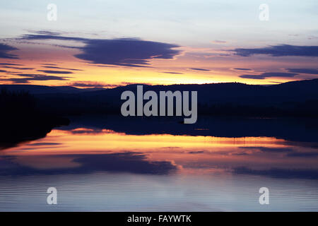 Setting sun over mountains with colours reflected in a lake with gentle ripples on the water evoking a scene of - Stock Photo