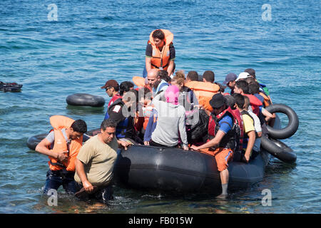 Syrian refugees cross from Turkey in a rubber raft to land on a beach on the Greek island of Lesvos/Lesbos - Stock Photo