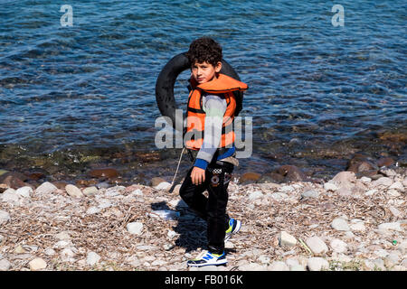 Young Syrian refugee arriving on the island of Lesvos plays with an inner tube after crossing from Turkey in a raft. - Stock Photo