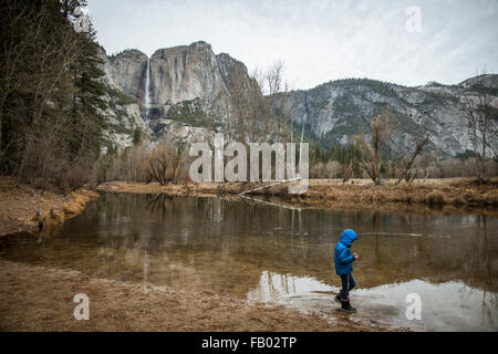 Young child  walking the edge of the river in Yosemite Valley in fall.Wearing a blue winter coat with hood. near - Stock Photo