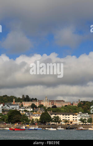 The Britannia Royal Naval College (HMS Dartmouth) dominates the skyline above Dartmouth, Devon, on a partly-cloudy - Stock Photo