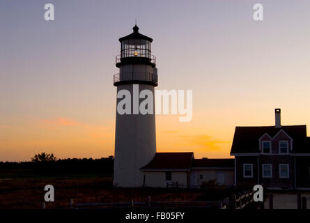 Sunset behind Cape Cod (Highland) lighthouse on Cape Cod in Massachusetts, on an early summer evening. - Stock Photo