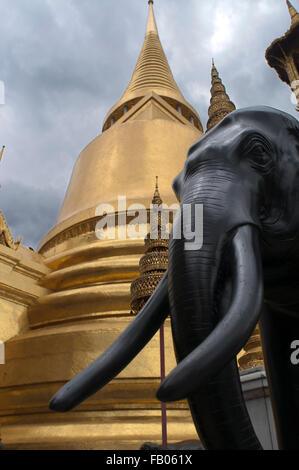 Golden Stupa and stone Guardian Wat Phra Kaew near the Royal Grand Palace Bangkok Thailand. Guardian giant in front - Stock Photo