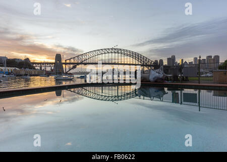 Beautiful sunrise scene at Sydney Harbour Bridge with dramatic sky colour and reflection