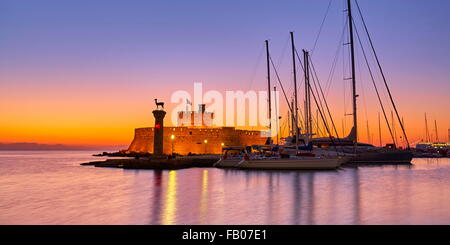Mandraki harbour and fortress Agios Nicolaos before sunrise, Rhodes town, Rhodes Island, Greece, UNESCO - Stock Photo