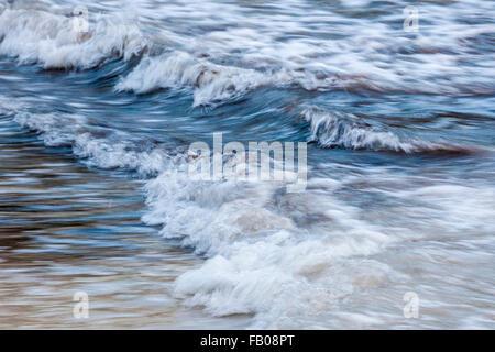 Blue foamy ocean waves breaking in shallow water, in-camera motion blur. - Stock Photo