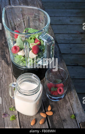 Blender with healthy smoothie ingredients - almond milk, fresh fruit, baby kale - on rustic wood table. - Stock Photo