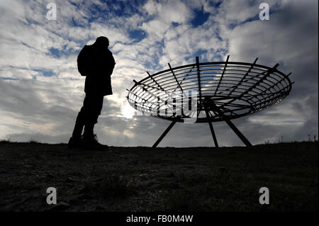 A walker stops to admire the view of The Halo panopticon on the hills above Haslingden, Lancashire as bad weather - Stock Photo